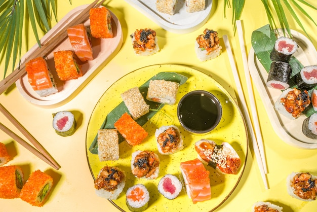 Sushi rolls set with rice and fish, soy sauce and chopsticks on yellow surface, trendy daylight flatlay