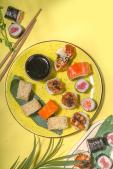 Sushi rolls set with rice and fish, soy sauce and chopsticks on yellow wall, flat lay
