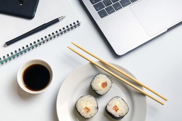 Sushi rolls snacking at work. break time for sushi eating with soy sauce.