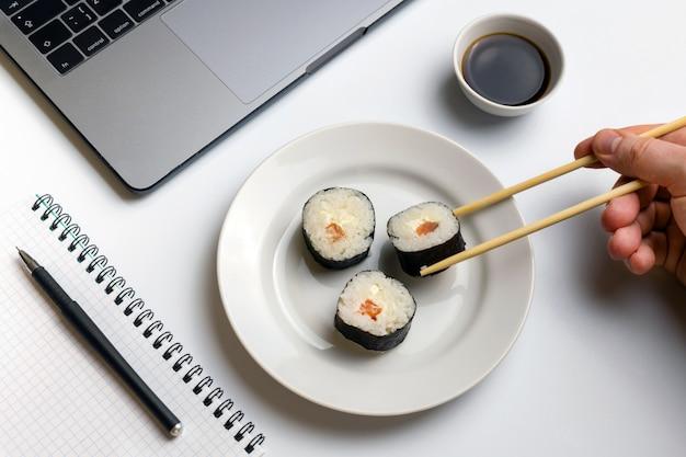 Sushi rolls snacking at work. break time for sushi eating