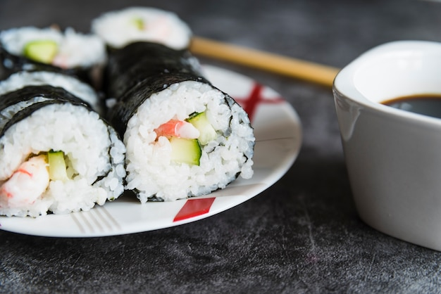 Суши роллы, соевый соус и палочки для еды
