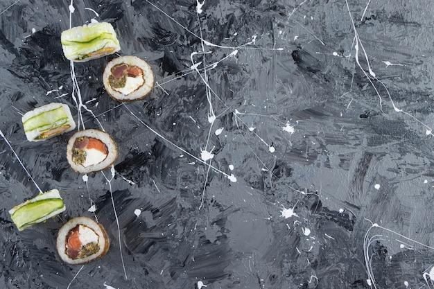 石の背景に巻き寿司、醤油、わさび、生姜のピクルス。