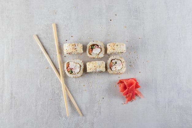 Суши-роллы, соевый соус, васаби и маринованный имбирь на каменном фоне.