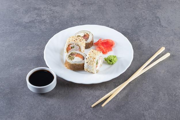 Суши-роллы, соевый соус, васаби и маринованный имбирь на каменной поверхности.