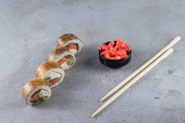 Sushi rolls, soy sauce, wasabi and pickled ginger on stone background.