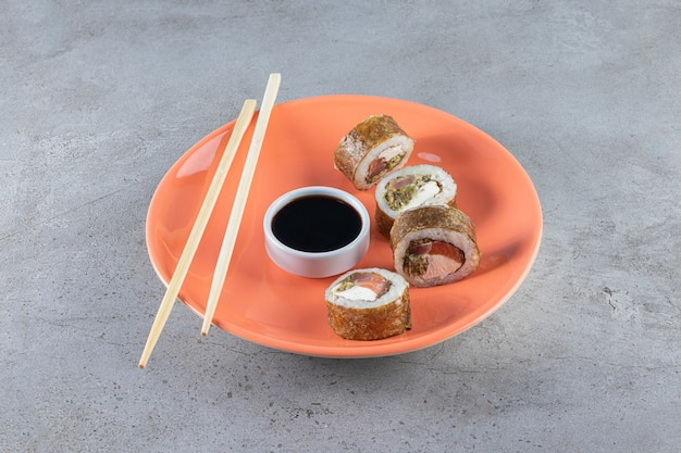 Sushi rolls, soy sauce, wasabi and pickled ginger on stone surface.