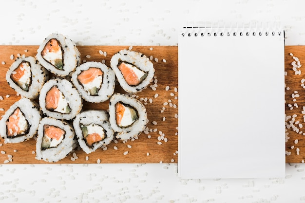 Sushi rolls and spiral notepad on wooden tray with splatter of uncooked rice