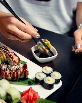 Involtini di sushi conditi con salsa e sesamo