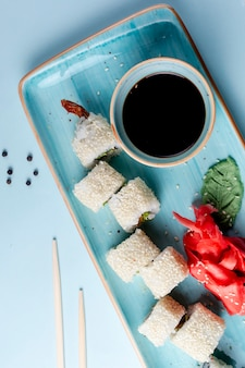 Sushi rolls topped with sesame and side sauce