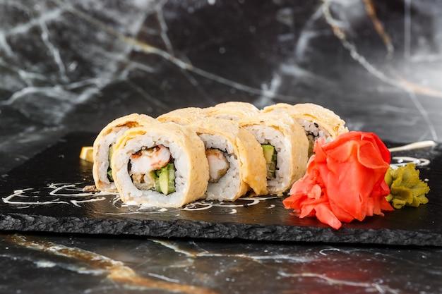 Суши роллы с авокадо, угрем, огурцом и сливочным сыром внутри на черный сланец, изолированные на черном фоне мрамора. калифорнийские роллы покрыты омлетом суши-меню. горизонтальное фото.