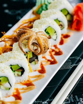 Sushi rolls with baby octopus avocado topped with sesame
