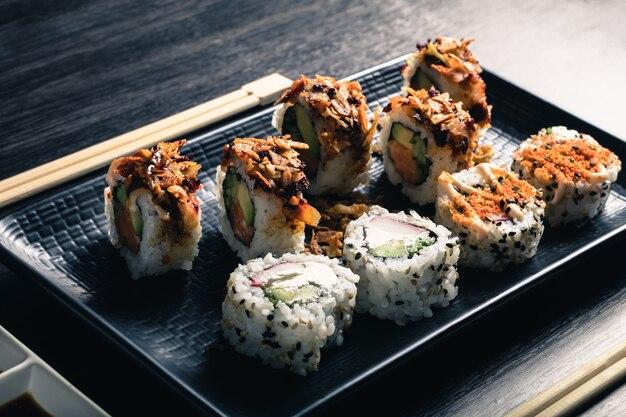 Sushi rolls with chopsticks on dark wood table