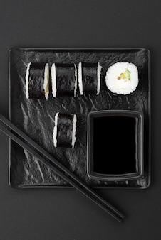 Суши роллы с палочками на тарелке