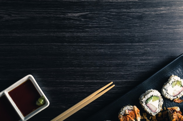 Sushi rolls with chopsticks and soy sauce on dark background. copyspace and top view