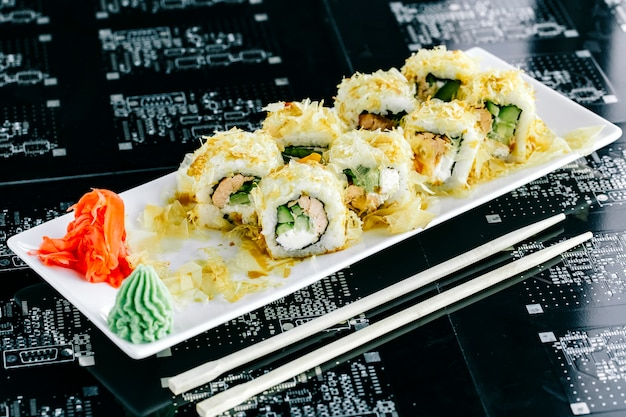 Sushi rolls with cooked salmon and cucumber served with ginger and wasabi