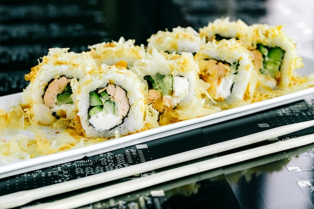 Sushi rolls with cooked salmon and cucumber