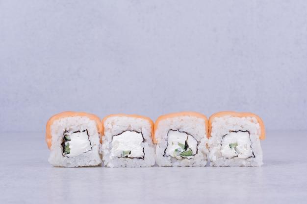 Rotoli di sushi con crema di formaggio su sfondo grigio