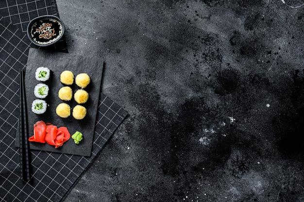 Суши роллы с огурцом, лососем и креветками на каменном подносе. черный фон. вид сверху. пространство для текста