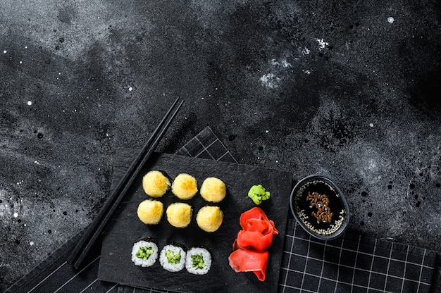 Sushi rolls with cucumber, salmon and shrimp on a stone tray. black background. top view. space for text