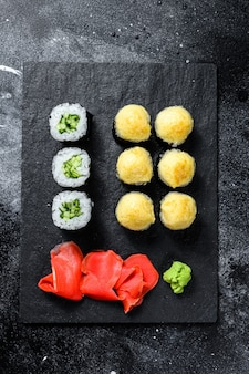 Sushi rolls with cucumber, salmon and shrimp on a stone tray. black background. top view