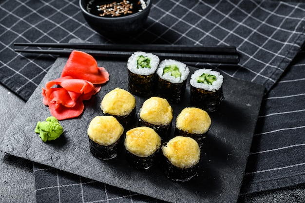 Sushi rolls with cucumber, salmon and shrimp on a stone tray. black surface. top view