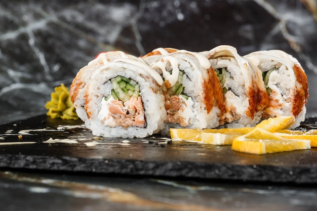 Суши роллы с огурцом, приготовленным на пару лососем, угрем и плавленым сыром внутри на черном сланце изолированы. филадельфия унаги ролл суши. суши-меню. горизонтальное фото.