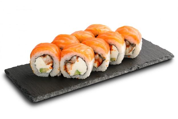 Суши-роллы с угрем, лососем, авокадо, икрой летучей рыбы и плавленым сыром внутри, изолированные на белом