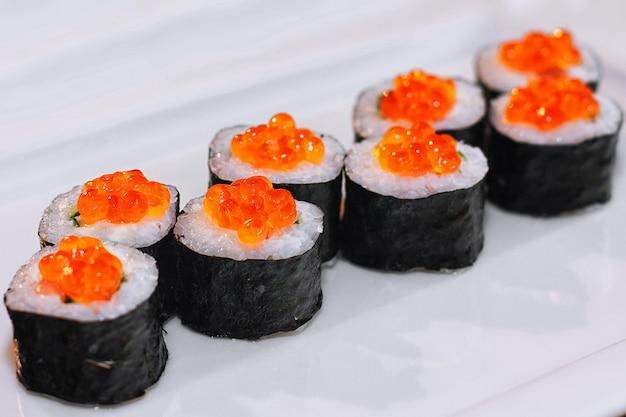 Суши-роллы с рыбой, икрой, сливочным соусом, авокадо, на белой тарелке