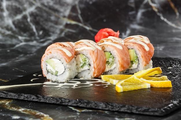 Суши роллы с пламенным лососем, огурцом и плавленым сыром внутри на черный сланец, изолированные на черном фоне мрамора. филадельфия ролл суши с огурцом. суши-меню. горизонтальное фото.