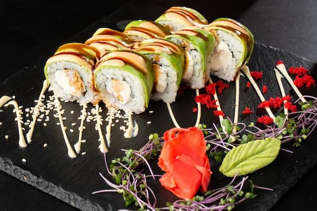 Суши-роллы с жареными темпурными креветками, авокадо, омлетом и сливочным сыром внутри. ,