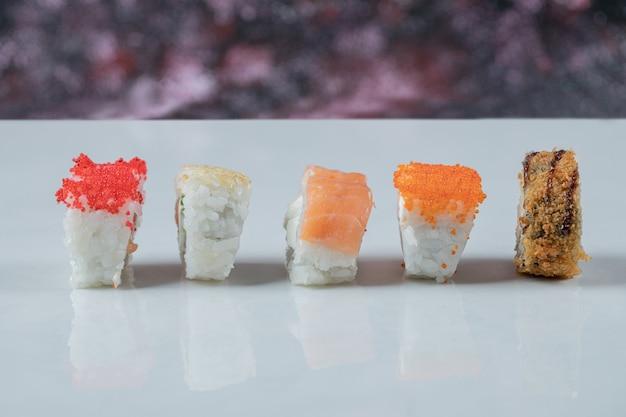 Rotoli di sushi con ingredienti misti isolati sul tavolo bianco.