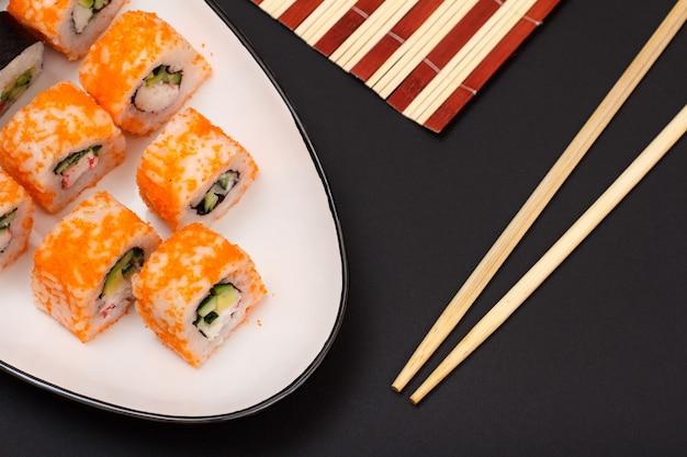 Суши-роллы с нори, рисом, кусочками авокадо, огурцом, икрой летучей рыбы на керамической тарелке и деревянных палочках. черный фон. вид сверху.