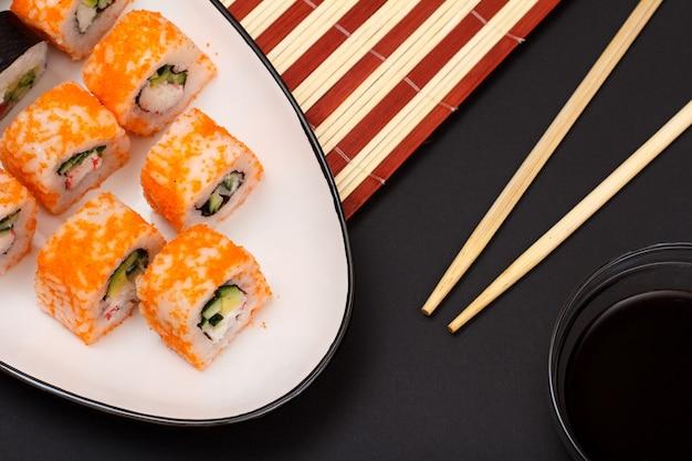Суши-роллы с нори, рисом, кусочками авокадо, огурцом, икрой летучей рыбы на керамической тарелке. чаша с соевым соусом и деревянными палочками. черный фон.