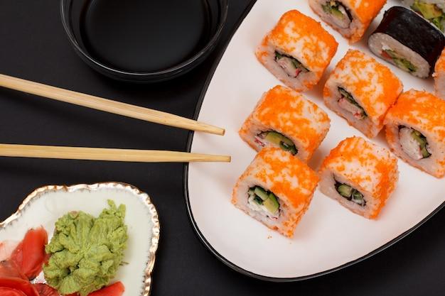 海苔、ご飯、アボカド、きゅうり、空飛ぶ魚卵をセラミックプレートに載せた巻き寿司。赤生姜の酢漬けとわさびの盛り合わせ。醤油と木の棒でボウル。黒の背景。