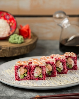 Sushi rolls with pink rice and cream cheese.