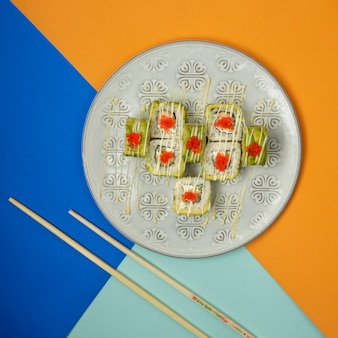 Sushi rolls with red caviar on a colorful table.