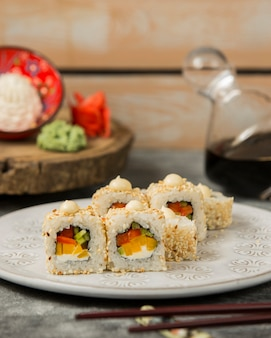 Sushi rolls with red and yellow bell pepper, cucumber topped with sesame