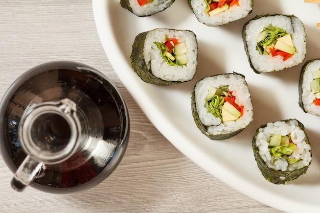 초밥은 쌀, 아보카도, 오이, 붉은 피망, 양상추 잎을 세라믹 접시에 얹은 롤입니다. 간장과 유리 병입니다. 평면도
