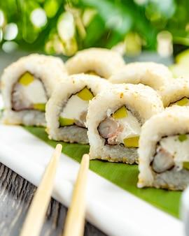 Involtini di sushi con riso, gamberi, avocado e crema di formaggio con salsa di soia sul tavolo