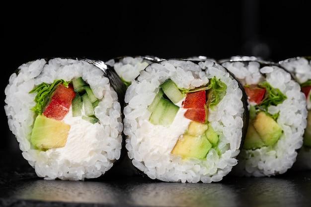 Суши роллы с салатом, авокадо, огурцом, перцем и сливочным сыром внутри.