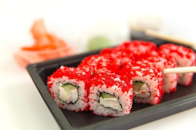 白い木製のテーブル、マクロにサーモンとキャビアを添えた巻き寿司。
