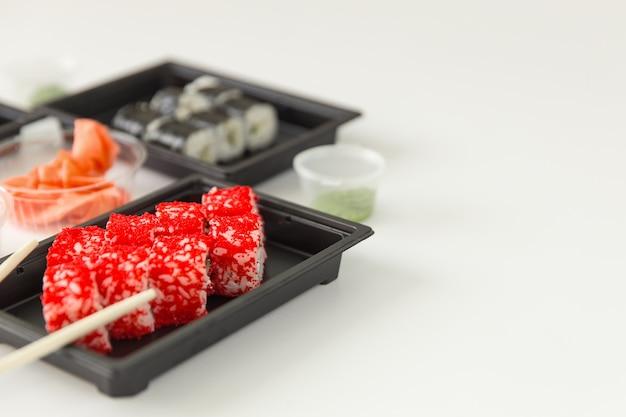 白い木製のテーブル、コピースペースにサーモンと生姜を添えた巻き寿司。