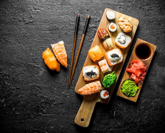 まな板に鮭と野菜を添えた巻き寿司と箸。黒の素朴な背景に