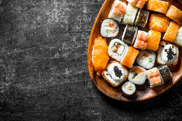 Суши-роллы с лососем и овощами на деревянной тарелке. на темном деревенском фоне