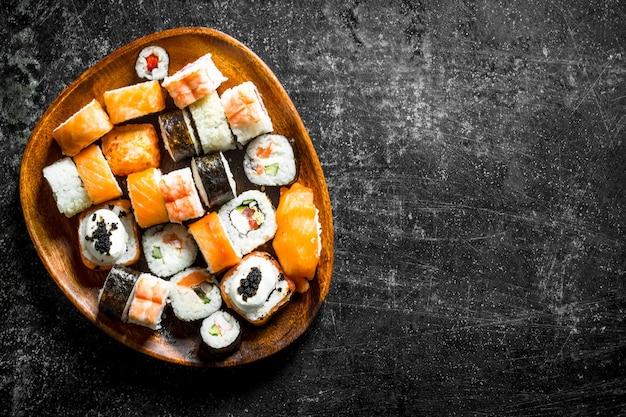 鮭と野菜を木の板に巻いた巻き寿司。暗い素朴な背景に