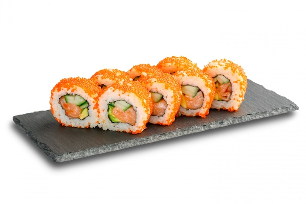 Sushi rolls with salmon, avocado, flying fish caviar and cucumber inside isolated on white .