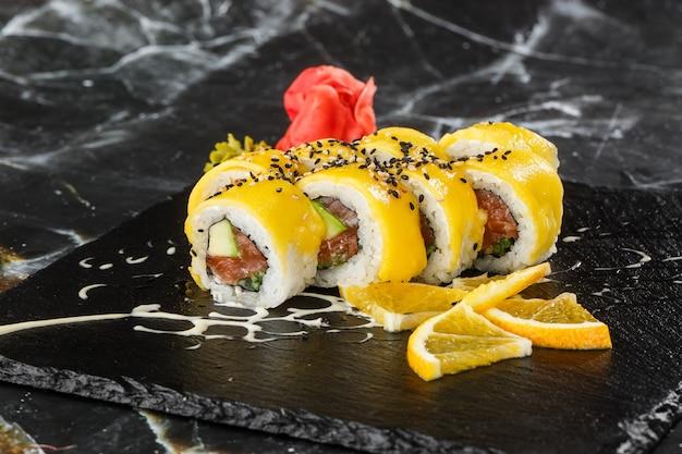 Суши роллы с лососем, авокадо, омлетом внутри и манго сверху. суши роллы с лососем на черном фоне мрамора. суши-меню. японская еда. горизонтальное фото.