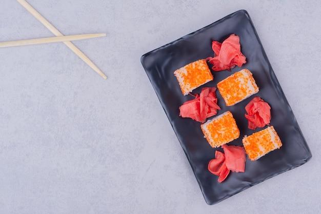 Rotoli di sushi con salmone in un piatto di ceramica nera.