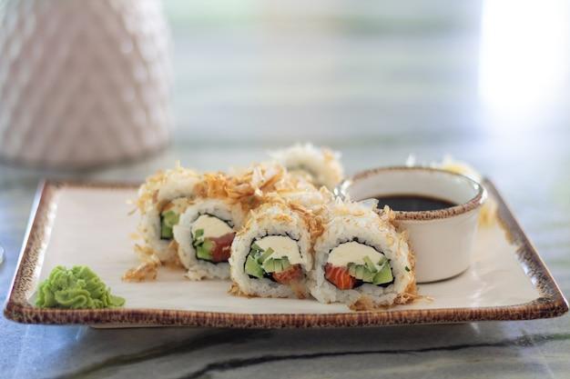コピースペースを持つ大理石のテーブルにサーモン、キュウリ、フィラデルフィアのクリームチーズの巻き寿司。寿司メニュー。日本の食べ物。