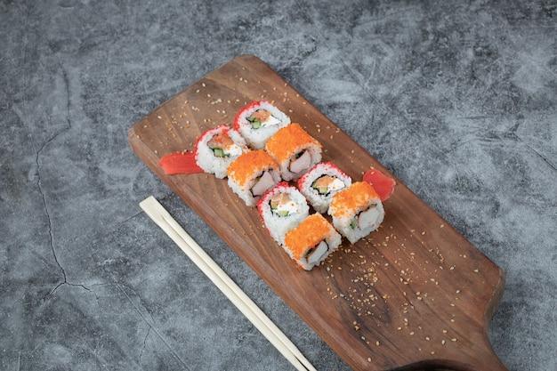 Суши-роллы с морепродуктами и красной икрой, изолированные на деревянном блюде.